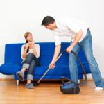 man vacuums around sitting woman
